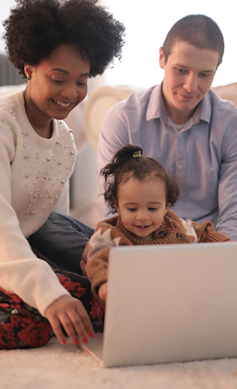 Young family on laptop in living room