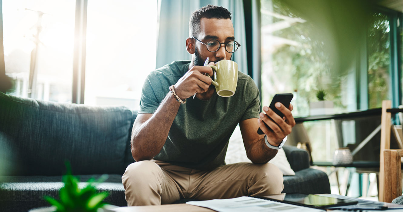 Man on phone drinking coffee at home
