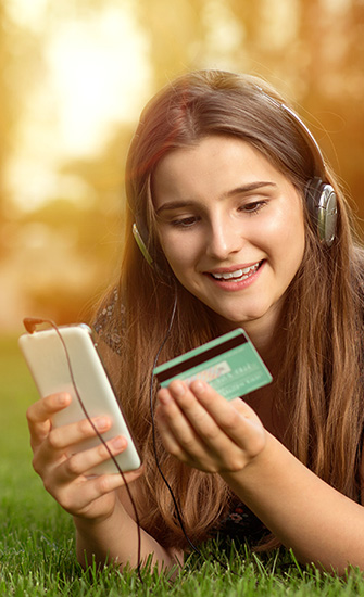 Teenager with debit card and phone
